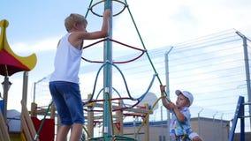 Ungar som spelar på lekplatsen, går upp trappan Aktiva utomhus- sportar arkivfilmer