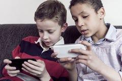 Ungar som spelar på smartphonen Royaltyfri Foto
