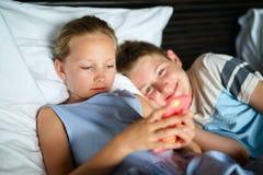 Ungar som spelar på smartphonen royaltyfri fotografi