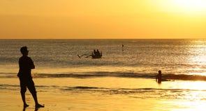 Ungar som spelar på stranden med fiskarefartyget i Bali, Indonesien under solnedgång på stranden royaltyfri fotografi