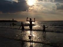 Ungar som spelar på stranden på solnedgången Fotografering för Bildbyråer