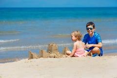 Ungar som spelar p? en strand Tv? barn bygger en sandslott p? havskusten Familjsemester på en tropisk semesterort Resa med royaltyfri fotografi
