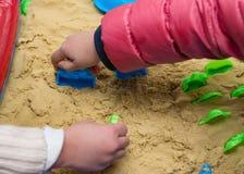 Ungar som spelar sand och plast-, gjuter arkivfoto