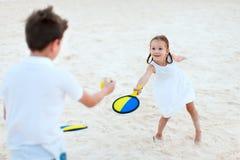 Ungar som spelar strandtennis Arkivfoto