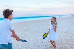 Ungar som spelar strandtennis Arkivbild
