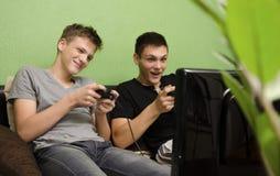 Ungar som spelar videospelet i deras rum royaltyfria foton