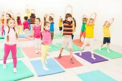 Ungar som sträcker under gymnastisk kurs i idrottshall arkivbild