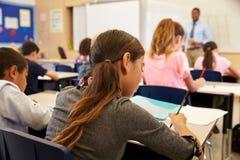 Ungar som tar anmärkningar i en grundskolakurs arkivfoto