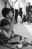 Ungar som tigger för encentmynt på den Bangkok gatan Arkivbild