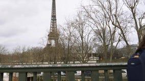 Ungar som tillbaka kommer till från skolan som går på Pont de Bir-Hakeim med Eiffeltorn arkivfilmer