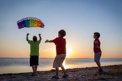 Ungar som tillsammans lanserar regnbågedraken Royaltyfri Fotografi