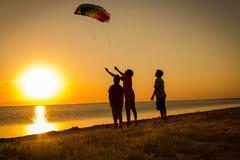 Ungar som tillsammans lanserar regnbågedraken Royaltyfri Bild