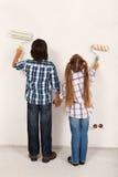 Ungar som tillsammans målar deras rum Arkivbild