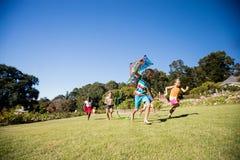 Ungar som tillsammans spelar under en solig dag med en drake arkivbilder