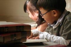 ungar som tillsammans studerar Arkivfoto