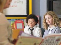 Ungar som tillsammans studerar i klassrum Arkivfoto