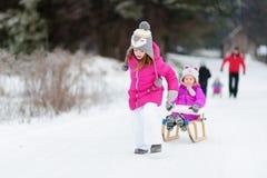 Ungar som tycker om sleightritt på vinterdag Royaltyfri Foto