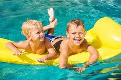 Ungar som tycker om sommardag på pölen Arkivfoto