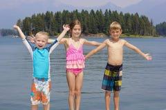 Ungar som tycker om sommarsemester på sjön Fotografering för Bildbyråer