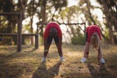 Ungar som utför sträcka övning under hinderkurs royaltyfri foto