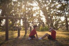 Ungar som utför sträcka övning under hinderkurs arkivfoton