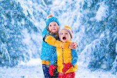 Ungar som utomhus spelar i vinter Fotografering för Bildbyråer