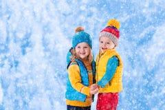 Ungar som utomhus spelar i vinter Arkivfoto