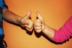 Ungar som visar två tummar upp på orange bakgrund Arkivfoto