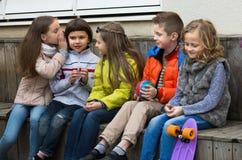Ungar som viskar i andra utomhus- öron Royaltyfria Bilder