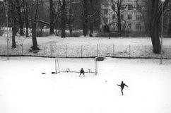Ungar spelar fotboll i vintertid Royaltyfri Bild