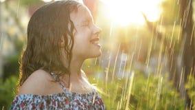 Ungar spelar i sommarregn Spela f?r barn som ?r utomhus- p? regnig dag Liten flicka som fångar regndroppar under tung dusch fall arkivfilmer