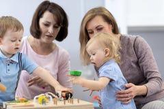 Ungar spelar med bildande leksaker i barnkammare royaltyfria bilder