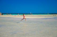 Ungar spelar och kör på den berömda sandiga stranden av Elafonissi, Kreta, Grekland Arkivfoton