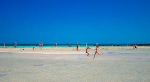 Ungar spelar och kör på den berömda sandiga stranden av Elafonissi, Kreta, Grekland Royaltyfri Foto