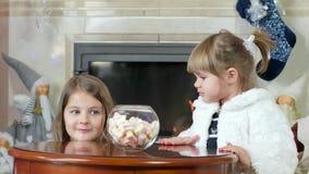 Ungar stjäler godisen, liten flickanederlag under en tabell, blick ut och hastigt greppgodismarshmallower, barn med en slug blick lager videofilmer