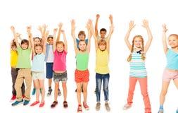 Ungar står tillsammans pojkar, och flickor stiger händer Arkivfoto