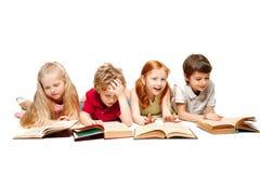 Ungarna pojke och flickor som lägger med böcker som isoleras på vit arkivbild