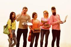 Ungdom med böcker, påsar och bärbara datorn Studenter vänner, grupp parar ihop att posera med studentattribut, vit bakgrund fotografering för bildbyråer