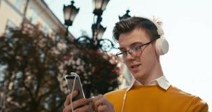 Ungdom och teknologi Den attraktiva unga grabben med blont hår, glasögon och fräknar pratar på mobiltelefonen och stock video