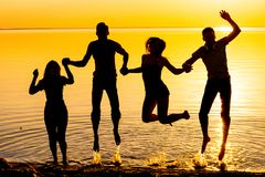 Ungdomar, grabbar och flickor, hoppar mot solnedgångbacen Royaltyfria Bilder