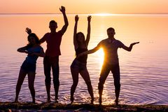 Ungdomar, grabbar och flickor, studenter dansar på solnedgångbac Royaltyfri Bild