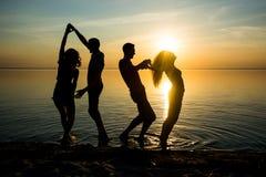 Ungdomar, grabbar och flickor, studenter dansar på stranden Royaltyfria Bilder