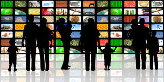 Ungdomar med barn som håller ögonen på televisionen 免版税库存图片