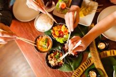 Ungdomar som äter i thailändsk restaurang arkivfoto