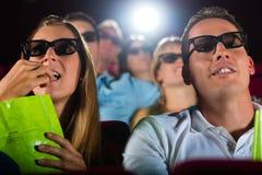 Ungdomar som håller ögonen på filmen 3d på bion Arkivfoton