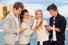 Ungdomar telefoner Arkivbild