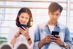 Ungdomaranv?nder smartphonen och ler, medan sitta p? fri tid begrepp isolerad teknologiwhite arkivfoto