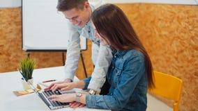 Ungdomararbetar genom att använda bärbara datorn och diskutera projektet i ett hemtrevligt kontor lager videofilmer