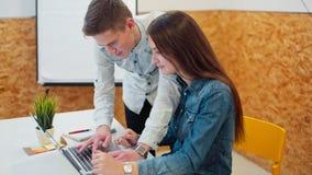 Ungdomararbetar tillsammans genom att använda bärbara datorn och diskutera projektet arkivfilmer
