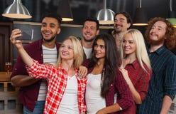 Ungdomargrupp i stången, lyckliga le vänner som tar det Selfie fotoet på bar för öl för cellSmart telefon royaltyfria bilder